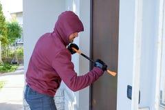 Assaltante que tenta forçar uma fechadura da porta usando uma pé de cabra imagem de stock