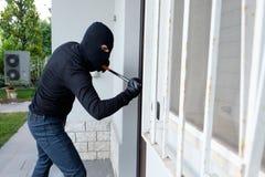 Assaltante que tenta forçar uma fechadura da porta usando uma pé de cabra fotos de stock