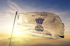 Assam state of India flag textile cloth fabric waving on the top sunrise mist fog stock photography