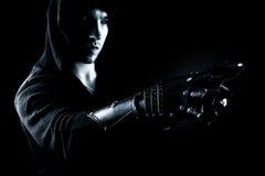 Assassin émotif, jeune et attirant dans les gants sur le fond noir Image libre de droits