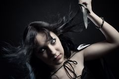 Assassin. Girl with dagger posing over dark background stock photos