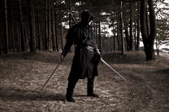 Assassin in the deep forest. Assassin with two swords in the deep forest Stock Photo