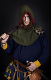Assassin is posing. Male wearing a cloak and holding club Royalty Free Stock Images