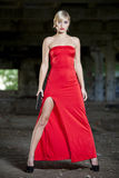 Assassin in red dress. Female assassin in vintage look with gun in old fabric ruins stock images