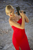 Assassin in red with gun. Beautiful assassin in red dress with gun playing a spy stock photo