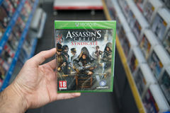 Assassin`s Creed Syndicate videogame on XBOX One. Bratislava, Slovakia, circa april 2017: Man holding Assassin`s Creed Syndicate videogame on Microsoft XBOX One Royalty Free Stock Photography