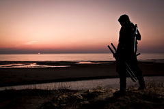 Assassin at the sea. Assassin with sword at the sea on sunset royalty free stock photos