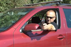 Assassin shooting from a moving car. Masked Assassin shooting from a moving car, aggressive driver stock photography