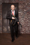 Assassin in suit and red tie holding machine gun Stock Photography