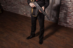 Assassin in suit and red tie holding machine gun Royalty Free Stock Photos