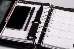 Assassinez le concept de planification - calendrier, téléphone portable et couteau photo libre de droits