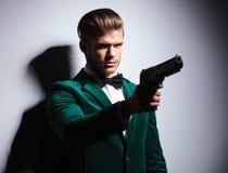 Assassino dell'emulo di personaggi famosi di James Bond giovane che indica la sua grande pistola Immagini Stock