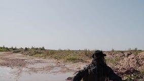Assassino em um casaco preto e com uma faca em sua mão que corre após alguém através do deserto video estoque