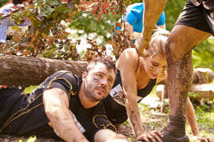 Assault course competitor helping others crawl under nets Stock Photography