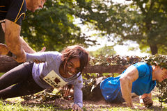 Assault course competitor helping others crawl under nets stock images