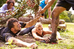 Assault course competitor helping others crawl under nets Royalty Free Stock Image