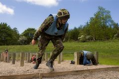 Assault course sprint. A UK soldier on assault course sprints from a wire obstacle wearing camoflage clothing and a kevlar helmt stock photo