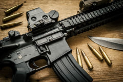 Assault rifle and bullets on the table. Assault rifle and bullets on old wooden table Stock Image
