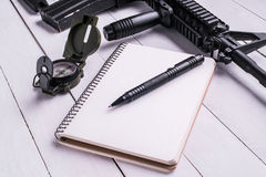 Assault rifle,compass, notebook with pen on desk. Assault automatic rifle,compass, notebook with pen on white table. Top view stock images