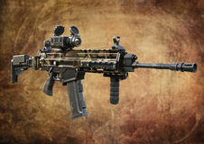 Assault rifle desert camouflage addition with tactical accessories front and rear sites , and a laser guided rifle scope on a grad. Ient background . 3d Royalty Free Stock Images