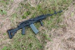 Assault rifle in the grass. Stock Photos