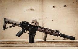 Assault rifle on a wooden table. Black assault rifle on a light wooden table stock photography