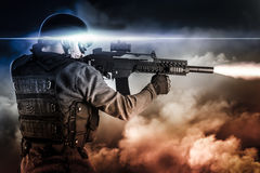 Assault soldier with rifle on apocalyptic clouds, firing. Assault soldier with rifle on apocalyptic Royalty Free Stock Photo