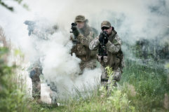 Assault of special forces. Soldiers walking through smoke on battle field Royalty Free Stock Image