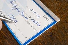 Assegno di firma della mano sopra lo scrittorio immagine stock libera da diritti