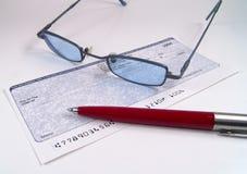 Assegno, penna e vetri immagine stock