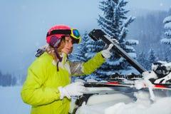 A asseguração da jovem mulher esquia no telhado do carro fotos de stock royalty free