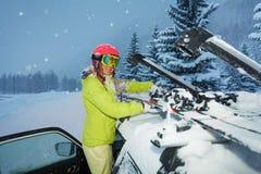 A asseguração da menina esquia no telhado do carro durante a queda de neve imagens de stock royalty free