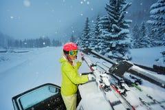 A asseguração da menina esquia no telhado do carro na noite fotografia de stock royalty free
