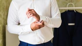 A asseguração do homem de negócio abotoa-se no close-up da luva da camisa em casa imagem de stock royalty free