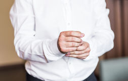 A asseguração do homem de negócio abotoa-se no close-up da luva da camisa em casa imagens de stock royalty free