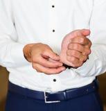 A asseguração do homem de negócio abotoa-se no close-up da luva da camisa em casa imagem de stock