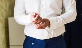 A asseguração do homem de negócio abotoa-se no close-up da luva da camisa em casa foto de stock