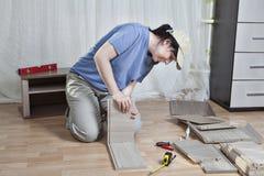 Assemblage houten meubilair, het deel van de vrouwenlijm van lade, op vloer Stock Foto's