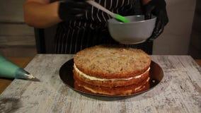 Assemblant le gâteau d'écrou-banane, enduisant du sirop, appliquant la crème, recouvrement bourrant, le processus entier de faire clips vidéos