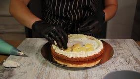 Assemblant les couches de gâteau d'écrou-banane, enduisant du sirop, appliquant la crème de beurre, bourrage de recouvrement clips vidéos
