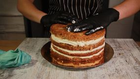 Assemblant les couches de gâteau d'écrou-banane, enduisant du sirop, appliquant la crème de beurre, recouvrement bourrant, le pro banque de vidéos