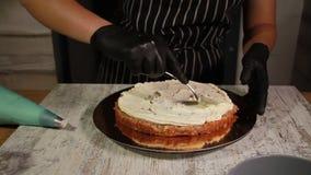 Assemblant les couches de gâteau d'écrou-banane, enduisant du sirop, appliquant la crème de beurre, remplissant remplissage, le p banque de vidéos