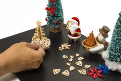Assemble Christmas tree by hand. Assemble Christmas tree on black sheet by hand with Santa and Snowman stock image