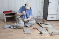 Assemble wooden furniture, a woman applies glue to chipboard edg Stock Images