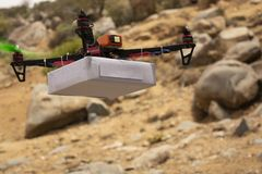 Assembled Drone quadcopter delivering a package with mountain as a background royalty free stock image