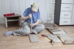 Assemblez les meubles en bois, une femme applique la colle à l'edg de carton gris Images stock