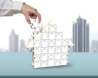 Assembling blank white puzzles in house shape Royalty Free Stock Photos