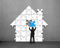 Assembling blue puzzles into house shape. On concrete wall Stock Images
