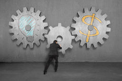 Assembling concrete gears with lamp and money symbol Stock Images