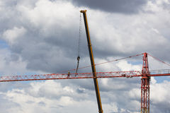 Assembling of crane on dramatic cloudy background. Dangerous height situation. Royalty Free Stock Images